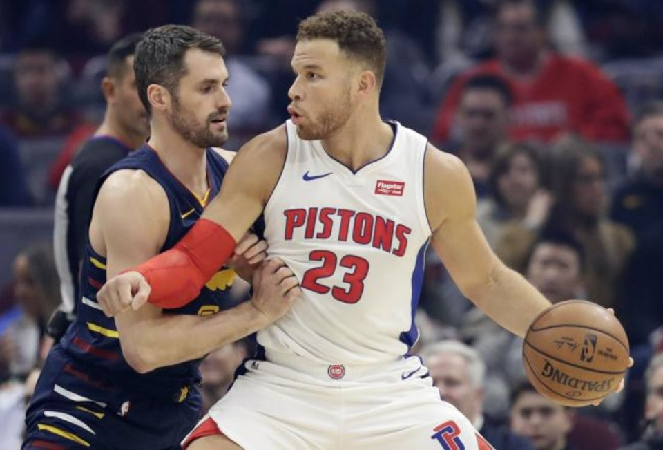 Photo -  Detroit Pistons' Blake Griffin, right, drives past Cleveland Cavaliers' Kevin Love in Tuesday night's game in Cleveland. Griffin scored 24 points in Detroit's 127-94 win. [AP Photo/Tony Dejak]