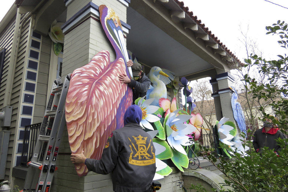 Photo -  Parade float workers Travis Keene, left, and Joey Mercer position a pelican while fellow crew member Chelsea Kamm, right, looks on while decorating a house in New Orleans on Friday, Jan. 8, 2021. All around the city, thousands of houses are being decorated as floats because the coronavirus pandemic has canceled parades that usually take place on Mardi Gras. (AP Photo/Janet McConnaughey)