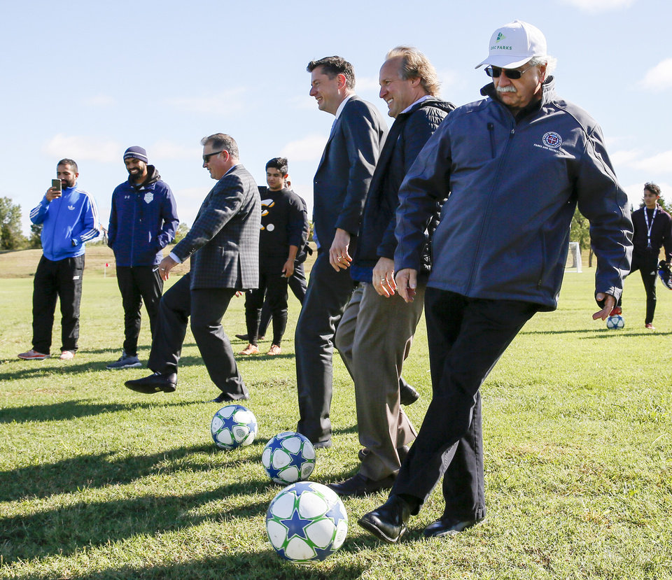 Photo -  Front to back, Parks Director Doug Kupper; Tim McLaughlin, OKC Energy FC partner; Mayor David Holt; and Kelly Gray, McLaughlin Family Foundation CEO, kick soccer balls at the dedication of new fields Wednesday at Lightning Creek Park. Eighty children who attended a free Energy FC clinic each left with a new soccer ball. [Photo by Nate Billings, The Oklahoman]