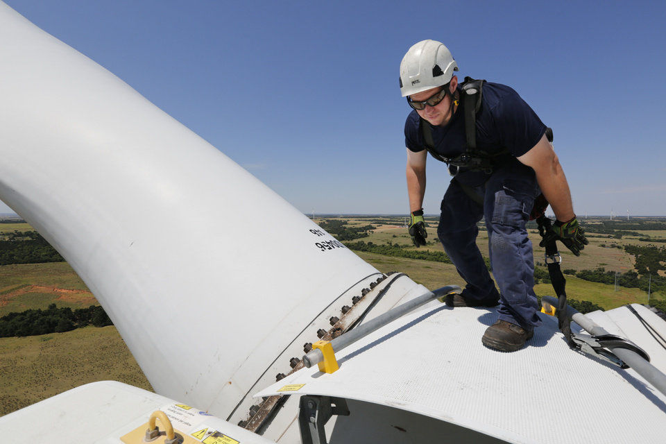 Photo -  NextEra Energy Resources wind technician Matthew Linthicum checks out the bolts securing the blades of a wind turbine in Minco. [Photo by Paul Hellstern, The Oklahoman]