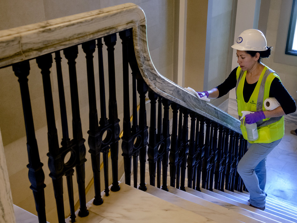 Photo - Erica Martinez wipes down the handrails while she works to sanitize the Oklahoma state Capitol as the building reopened to the public, and for legislative business on Monday, May 4, 2020, in Oklahoma City, Okla. after being closed due to the Coronavirus Pandemic.[Chris Landsberger/The Oklahoman]