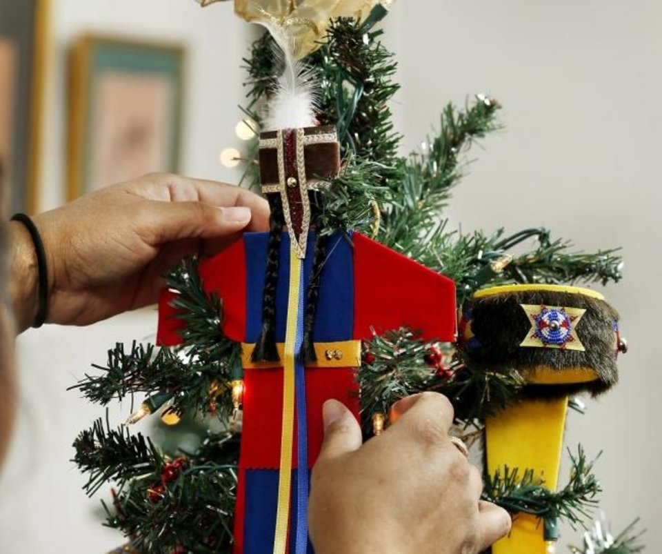 Photo -  A member of the Comanche Nation places decorations of the tree representing the tribe at the 2018 Red Earth Treefest. [The Oklahoman Archives]