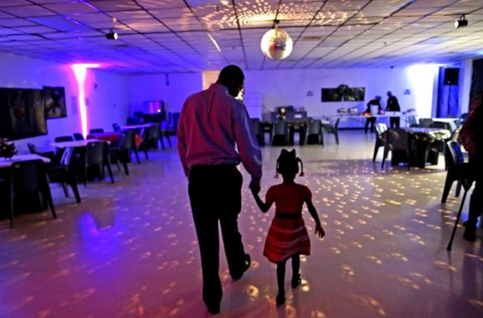 Photo -  Mark Warner leads his 4-year-old daughter into the daddy-daughter social event at Oklahoma City Transitional Living Center, a private community correctional center in south Oklahoma City. [Sarah Phipps/The Oklahoman]