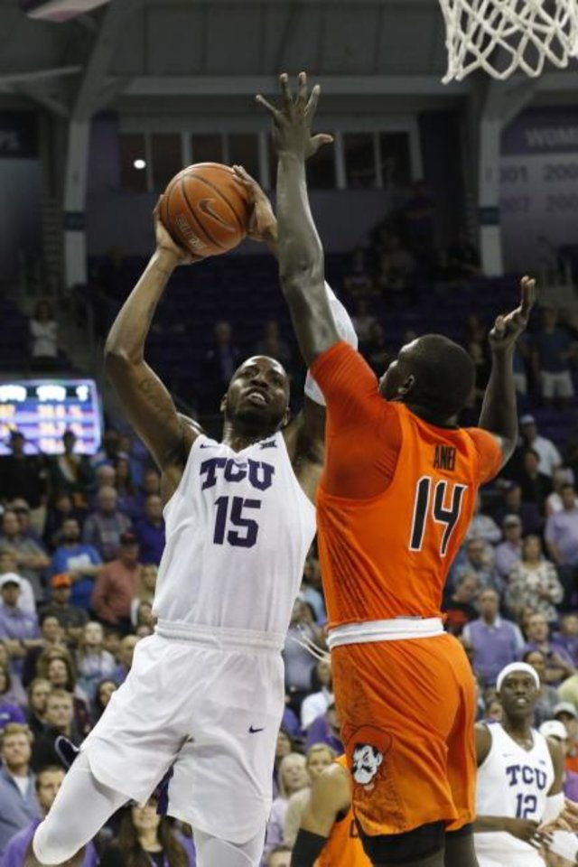 Photo -  TCU forward JD Miller (15) goes up for the winning shot as Oklahoma State forward Yor Anei (14) defends Wednesday in Fort Worth, Texas. [David Kent/Star-Telegram via AP]