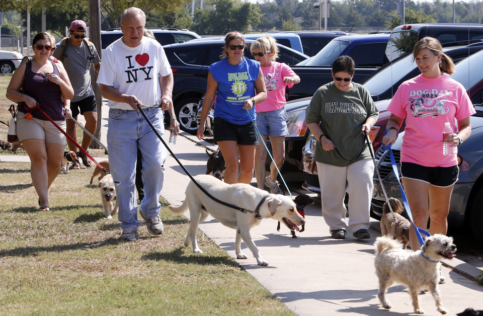 Photo -                    Owners walk their dogs in the inaugural Cindy Johnson Memorial Dog Walk during Dog Day Afternoon sponsored by Second Chance of Norman.                     PHOTOs BY STEVE SISNEY, THE OKLAHOMAN