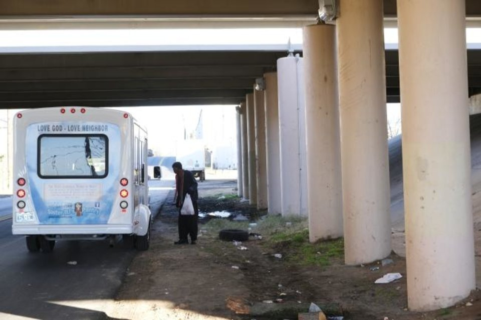 Photo -  A homeless man receives a sack of food from Sister BJ's Pantry bus on Dec. 6  at a homeless camp under an overpass in Oklahoma City. [Doug Hoke/The Oklahoman]