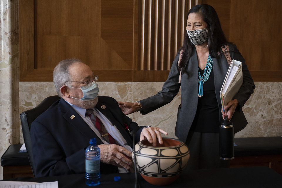 Photo -  Rep. Deb Haaland, D-N.M.,  delivers a gift to Rep. Don Young, R-Alaska, before the start of the Senate Committee on Energy and Natural Resources hearing on her nomination to be Interior Secretary, Tuesday, Feb. 23, 2021 on Capitol Hill in Washington. (Jim Watson/Pool via AP