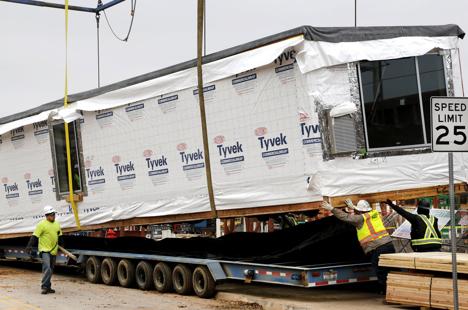 Photo -  A pre-fabricated hotel room is lifted off of a trailer to be stacked at the AC Hotel being built in east Bricktown. [Photo by Jim Beckel, The Oklahoman]