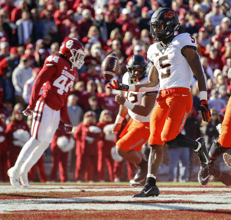 Photo - Oklahoma State's Justice Hill (5) tosses the ball to an official after a touchdown in the first quarter during a Bedlam college football game between the University of Oklahoma Sooners (OU) and the Oklahoma State University Cowboys (OSU) at Gaylord Family-Oklahoma Memorial Stadium in Norman, Okla., Nov. 10, 2018. Photo by Nate Billings, The Oklahoman