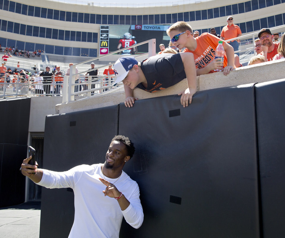 Photo - Former OSU running back Justice Hill takes a picture with fans during the Oklahoma State Cowboys spring practice at Boone Pickens Stadium in Stillwater, Okla., Saturday, April 20, 2019.  Photo by Sarah Phipps, The Oklahoman