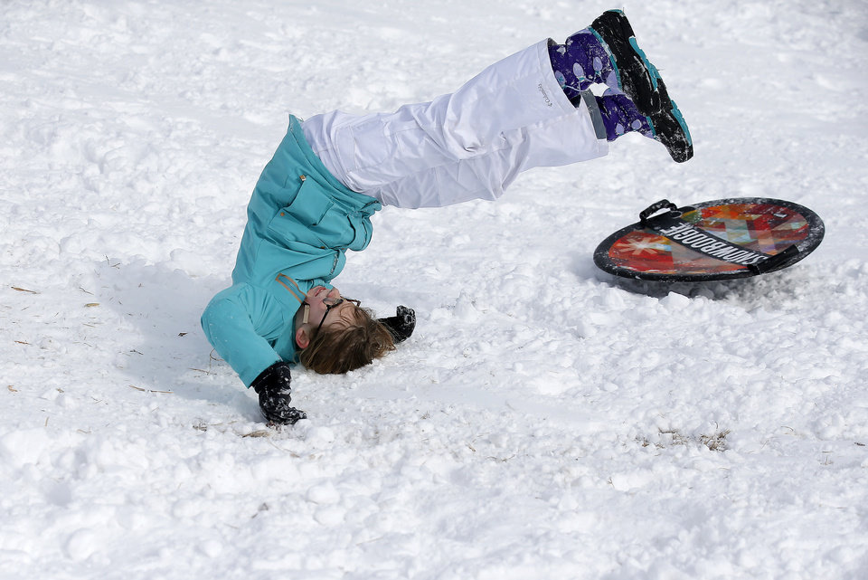 Photo - Ragan Moore flips after crashing while sledding on a hill along Hefner Road in Oklahoma City, Wednesday, Feb. 17, 2021. [Sarah Phipps/The Oklahoman]