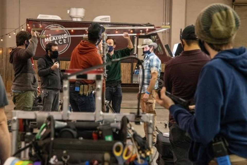 Photo -  Grip specialist Jon Shyock, center with cowboy hat, works with students on scene set-up at Prairie Surf Studio in downtown Oklahoma City. The food truck and string lighting is a set that will be shot as a nighttime scene. [PROVIDED]