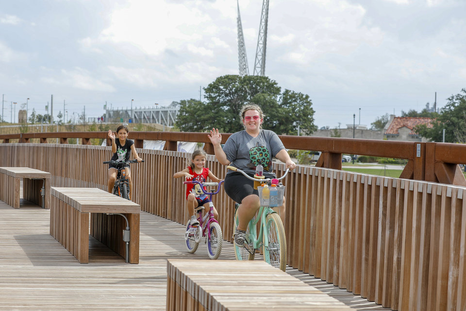 Photo - A family rides their bike across the bridge over Scissortail Lake during the grand opening weekend of Scissortail Park in Oklahoma City, Sunday, Sept. 29, 2019. (Alonzo Adams for The Oklahoman)