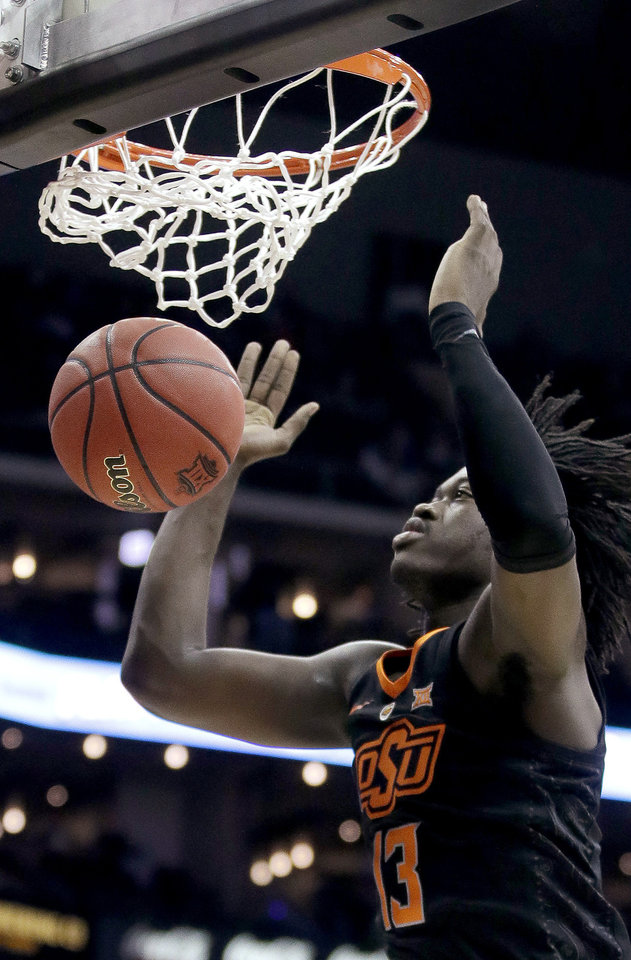Photo - Oklahoma State's Isaac Likekele watches the ball after his dunk during the first half of the team's NCAA college basketball game against TCU in the Big 12 men's tournament Wednesday, March 13, 2019, in Kansas City, Mo. (AP Photo/Charlie Riedel)