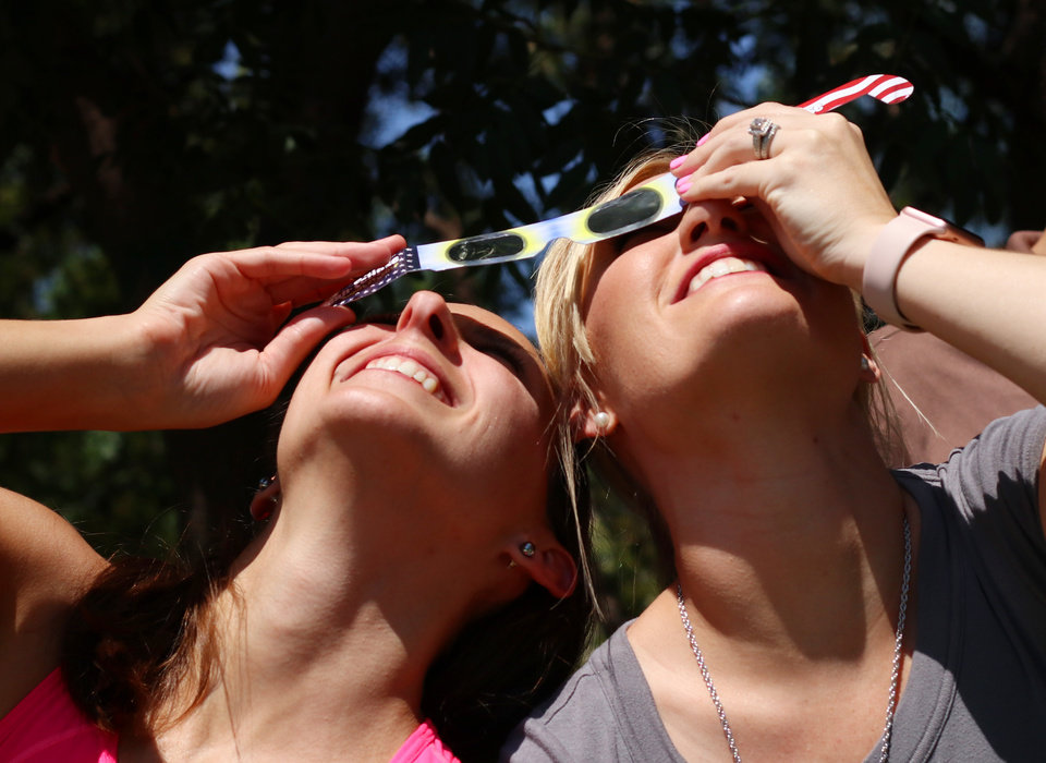 Photo - Rachel Olsen, left, and her co-worker at Devon, Kayla Young share a pair of glasses to view the eclipse during the great American solar eclipse party on the Great Lawn of the Myriad Botanical Gardens Monday, August 21, 2017. Photo by Doug Hoke, The Oklahoman