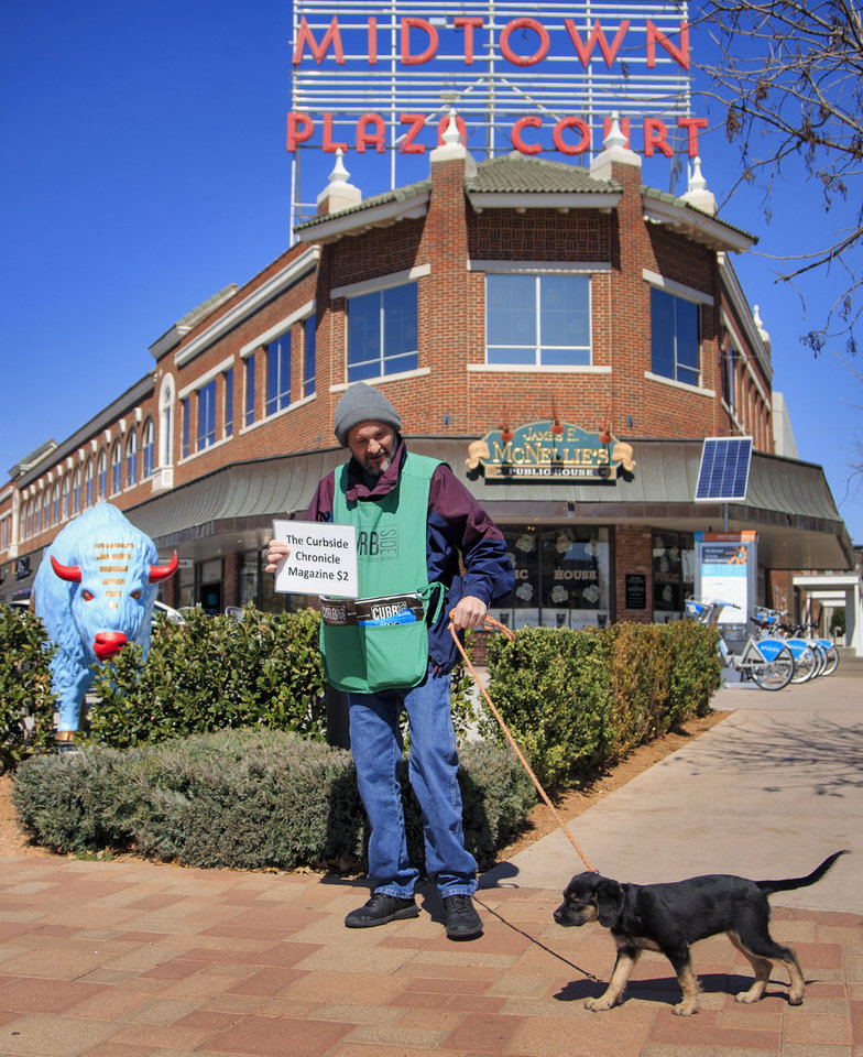 Photo -  Chazzie Davis walks the Midtown area with his dog, Fluffy, in March selling issues of the Curbside Chronicle. [Photo by Chris Landsberger, The Oklahoman Archives]