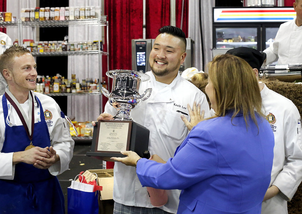 Photo -  Kevin Lee, the chef for the winning team, accepts his trophy. [Photo by Jim Beckel, The Oklahoman]