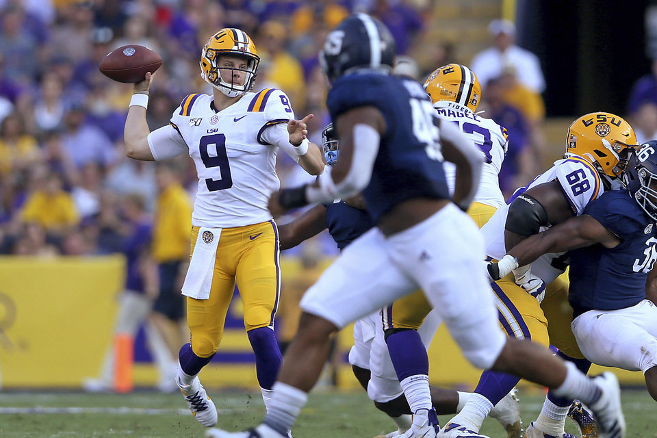 Photo - LSU quarterback Joe Burrow (9) throws in the first quarter of the team's NCAA football game against Georgia Southern in Baton Rouge, La., Saturday, Aug. 31, 2019. Burrow tied an LSU single-game record with five touchdown passes before halftime. (AP Photo/Michael Democker)
