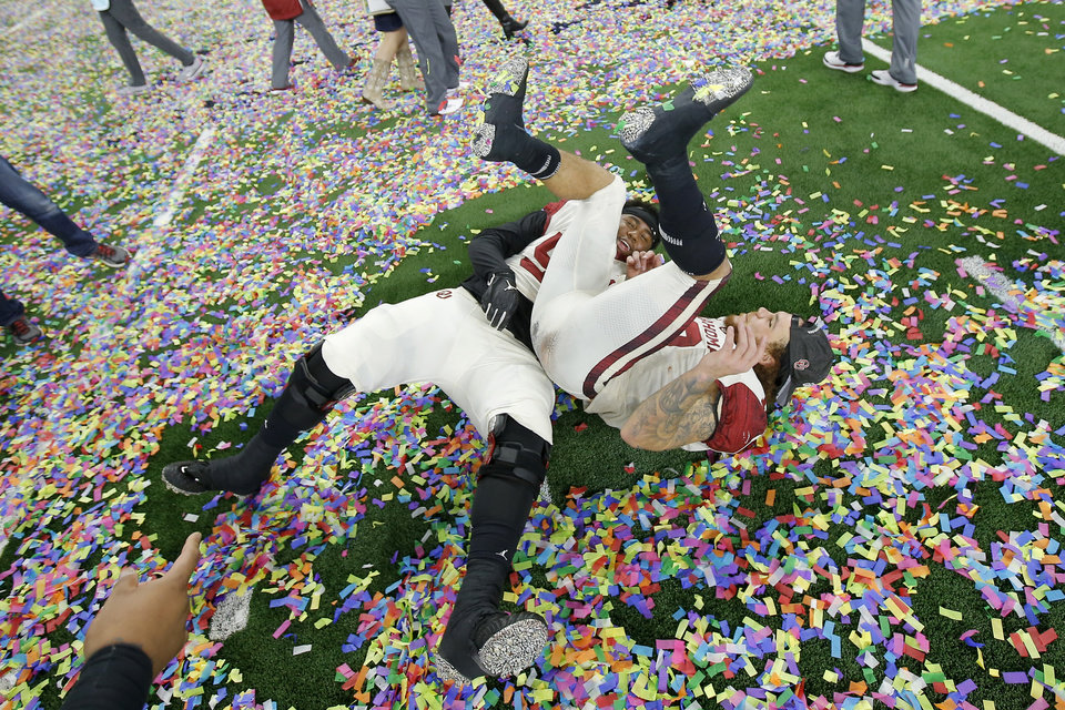 Photo -  Oklahoma's Tyrese Robinson, right, and Curtis Bolton celebrate after the Sooners beat Texas for the Big 12 championship. The Sooners' win helped put them in the college football playoffs, where they'll face No. 1-ranked Alabama on Dec. 29 in Miami. [PHOTO BY BRYAN TERRY, THE OKLAHOMAN]