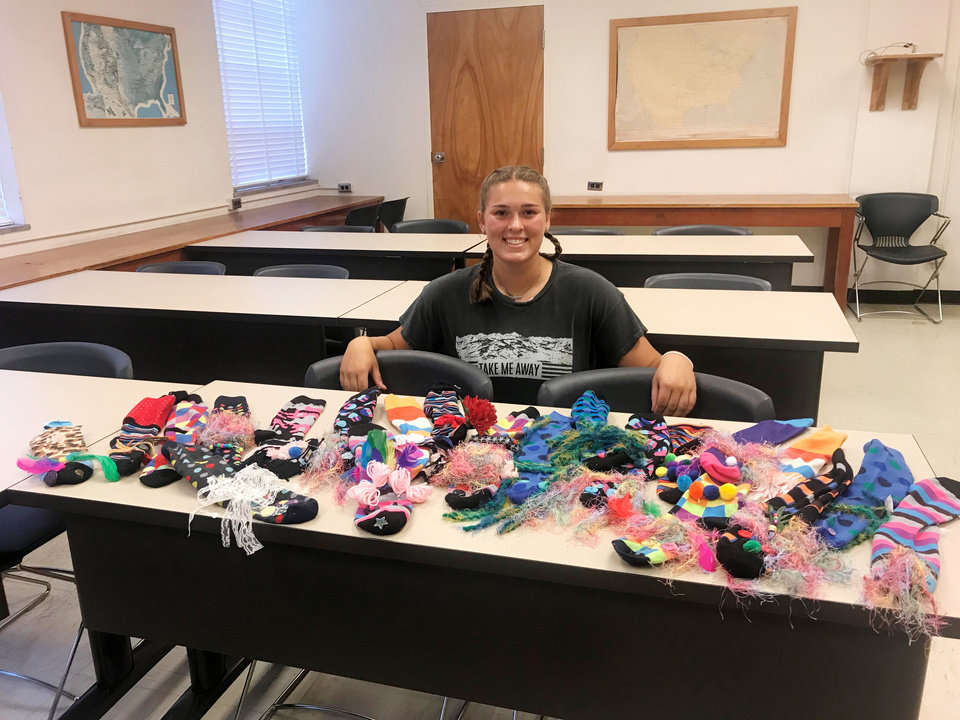 Photo - Taelor Brown, Pawnee County 4-H president, displays all the crazy sock puppets made at the workshop she led at the State 4-H Roundup in July. [PHOTO PROVIDED]