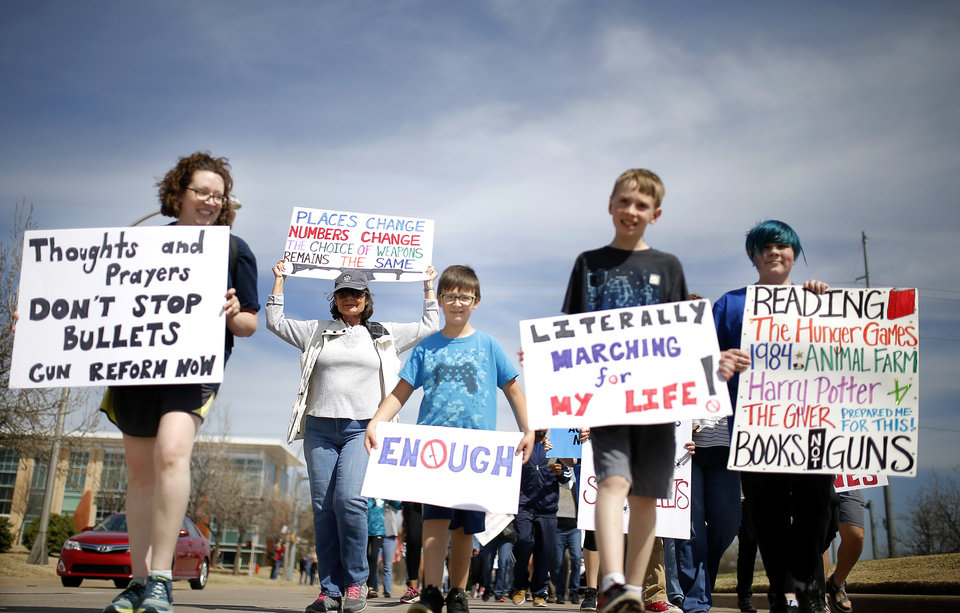 "Photo - People hold signs as they walk south on Lincoln Blvd., toward the state Capitol during the ""March for Our Lives"" rally in support of gun control, in Oklahoma City,  Saturday, March 24, 2018.  Photo by Sarah Phipps, The Oklahoman"