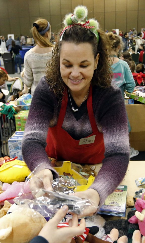 Photo - Adrianne Ayers, Midwest City, retrieves toys to distribute during the annual Red Andrews Christmas Dinner in the Cox Convention Center on Monday, Dec. 25, 2017 in Oklahoma City, Okla.  Photo by Steve Sisney, The Oklahoman