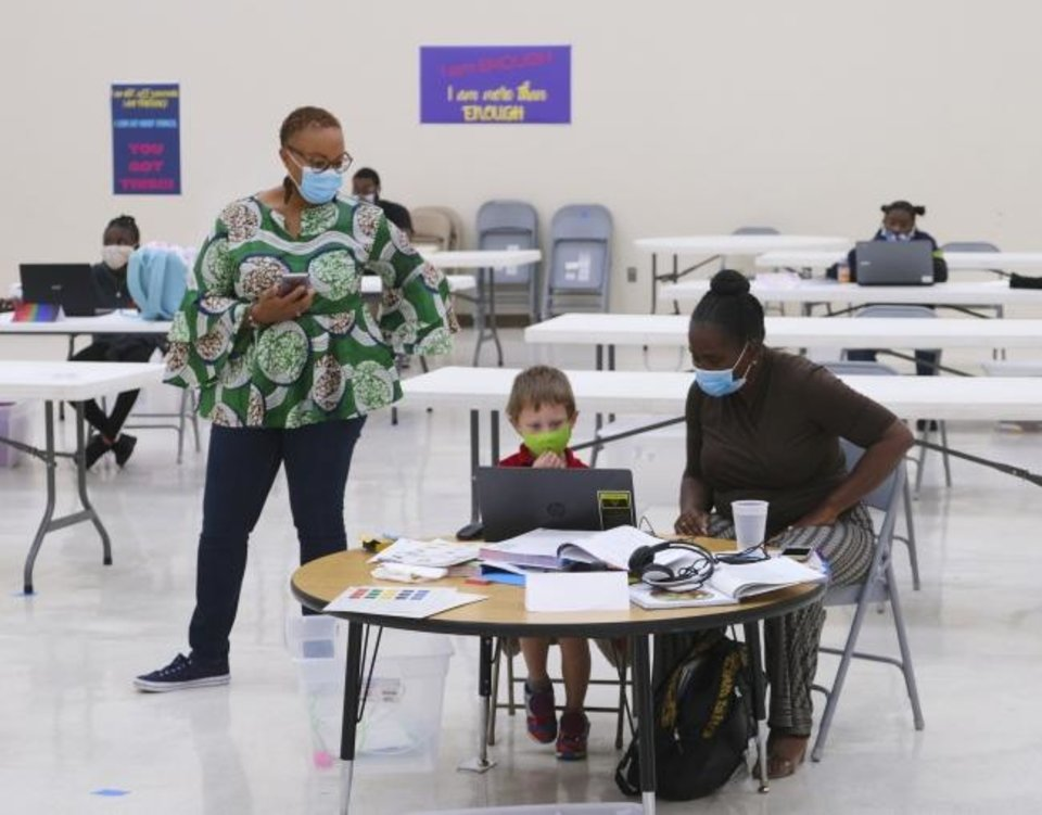 Photo -  Sharri Coleman, first lady of Fifth Street Missionary Baptist Church and community hope center site coordinator, checks on the progress of a student as Mrs. Williamson assists him with virtual school work Monday at Fifth Street, 801 NE 5. [Doug Hoke/The Oklahoman]