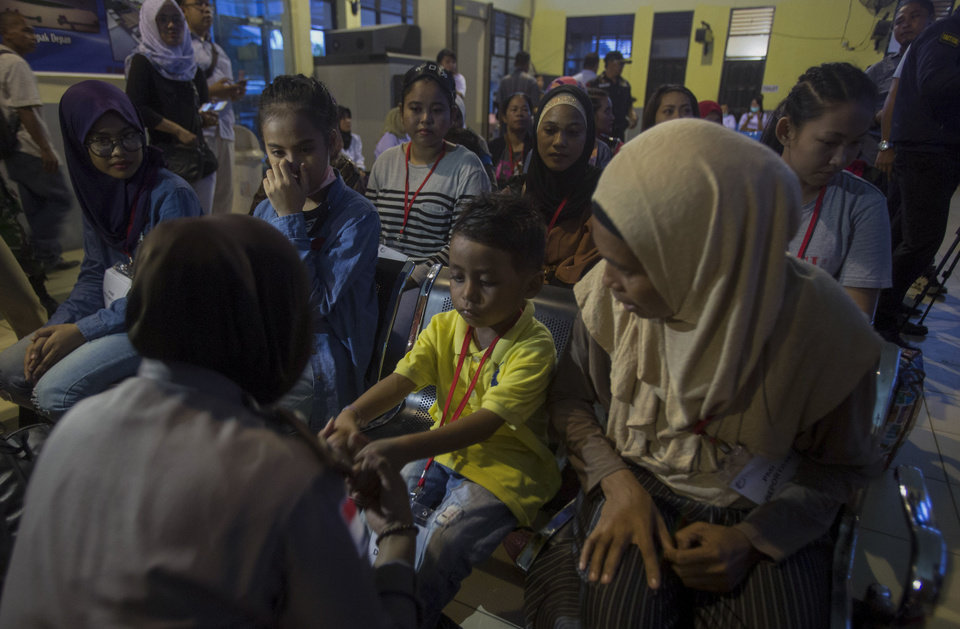 Photo -  A police officer plays with a child deported with his Indonesian family for working illegally in Malaysia, at an immigration office processing center in Nunukan, Indonesia, on Thursday, Dec. 6, 2018. (AP Photo/Binsar Bakkara)
