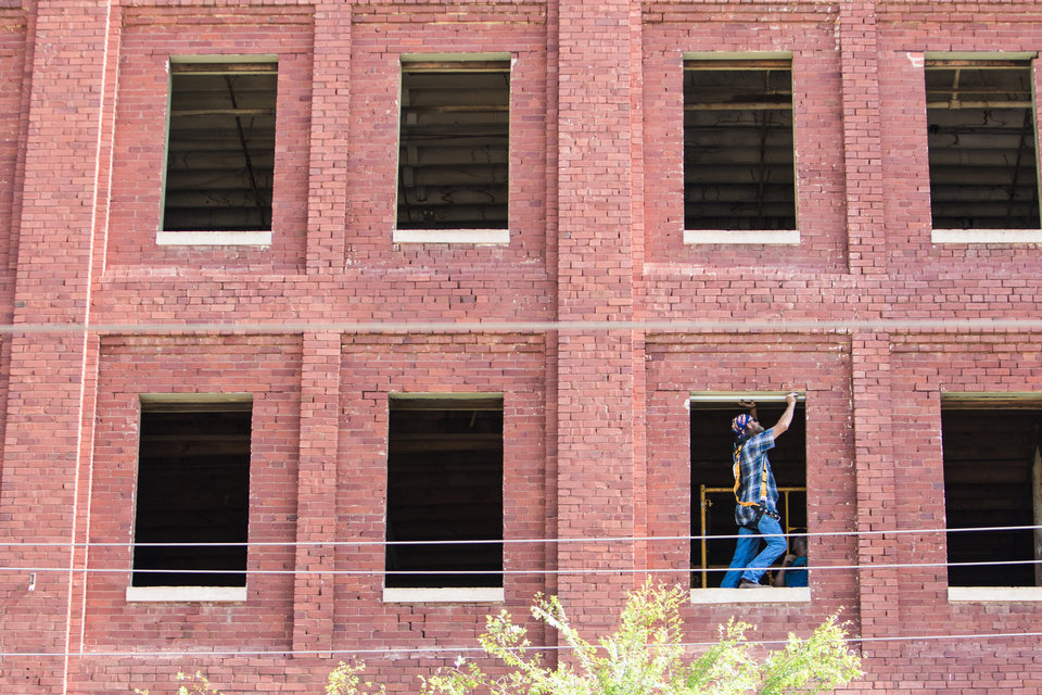 Photo -  A worker with Craig Smith Construction installs window frames at 101 E California Ave., formerly home to Spaghetti Warehouse. [Photo by Anya Magnuson, The Oklahoman]