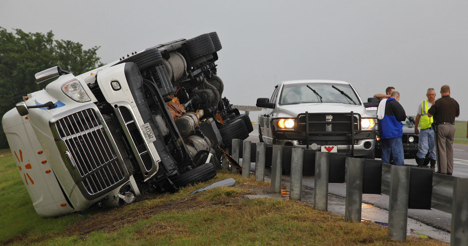Photo - Crews work the scene where a semi truck was swept off the road by a tornado west of El Reno, Tuesday, May 24, 2011. Photo by Chris Landsberger, The Oklahoman ORG XMIT: KOD