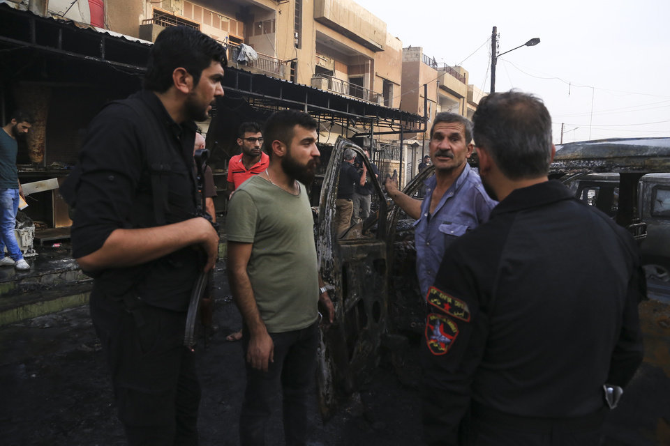 Photo -  People gather after a car bomb exploded in the town of Qamishli, Syria, Friday, Oct. 11, 2019. Turkish forces faced intense resistance by U.S.-allied Syrian Kurdish fighters on the third day of Ankara's offensive, as casualties mounted, international criticism of the campaign intensified and an estimated 100,000 people fled the violence. (AP Photo/Baderkhan Ahmad)