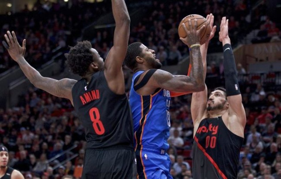 Photo -  Thunder forward Paul George, center, shoots between Trail Blazers center Enes Kanter, right, and forward Al-Farouq Aminu during the first half Thursday. [AP Photo/Craig Mitchelldyer]