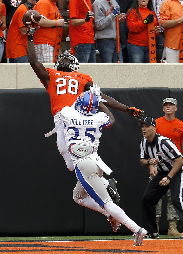 Photo - Oklahoma State's James Washington (28) makes a one-handed catch for a touchdown over Kansas' Courtney Arnick (28) during a college football game between the Oklahoma State University Cowboys (OSU) and the Kansas Jayhawks (KU) at Boone Pickens Stadium in Stillwater, Okla., Saturday, Oct. 24, 2015. Photo by Sarah Phipps, The Oklahoman