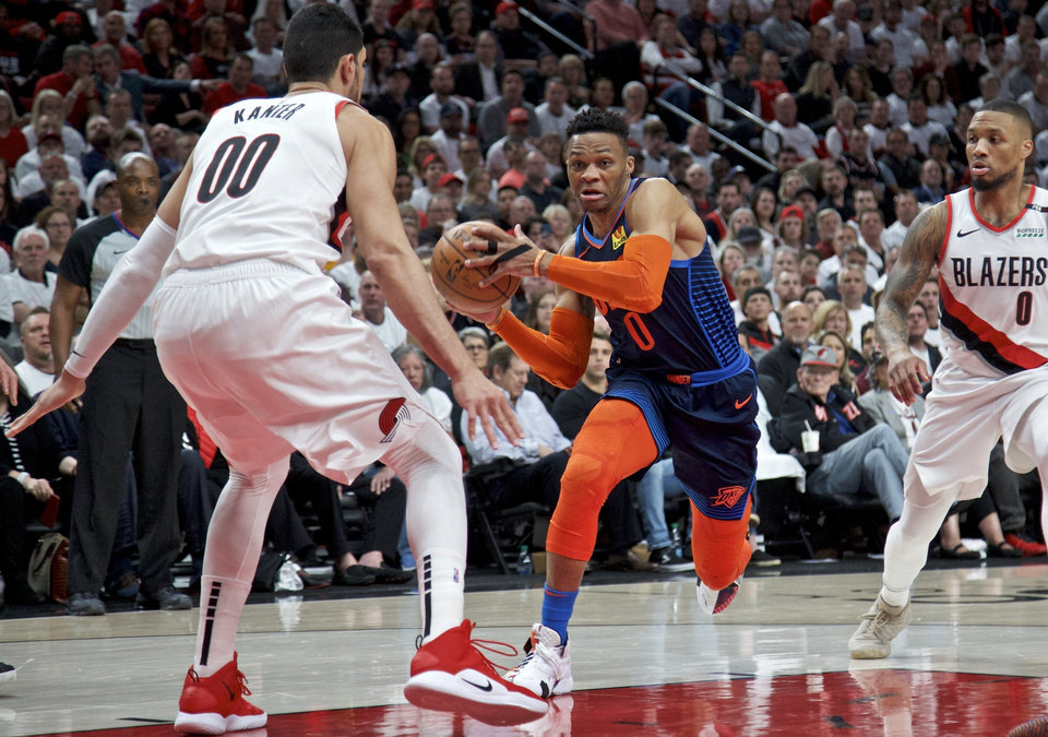 Photo - Oklahoma City Thunder guard Russell Westbrook, center, drives to the basket past Portland Trail Blazers guard Damian Lillard, right, and center Enes Kanter, left, during the first half of Game 5 of an NBA basketball first-round playoff series, Tuesday, April 23, 2019, in Portland, Ore. (AP Photo/Craig Mitchelldyer)