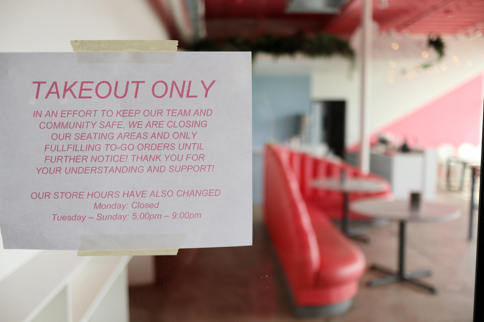 Photo - Take out only notice on the window of Cities Ice Cream at the Edmond Railyard location in Edmond, Wednesday, March 18, 2020.  [Photo by Doug Hoke/The Oklahoman]