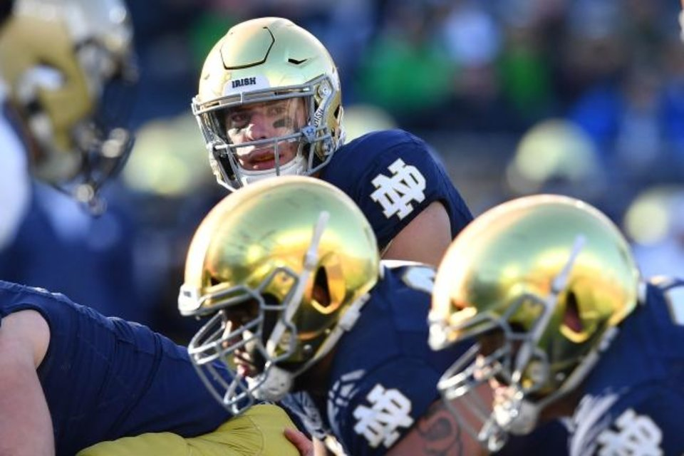 Photo -  Quarterback Ian Book (top) and the Fighting Irish will forgo independence this season to play in the ACC. [Matt Cashore/USA TODAY Sports]