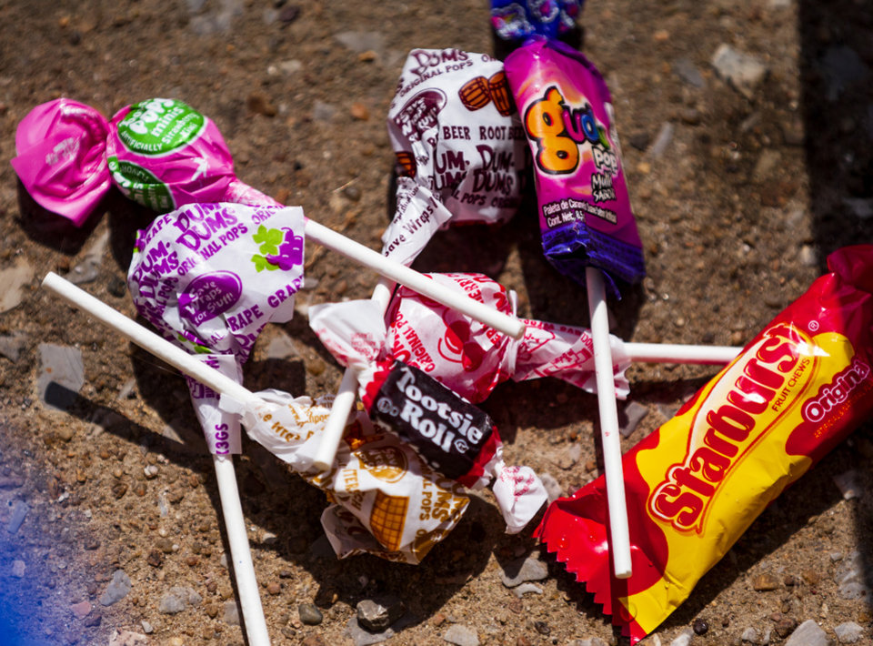 Photo - A small pile of candy is collected on the street during the Bethany Freedom Festival parade in Bethany, Okla. on Thursday, July 4, 2019.    [Chris Landsberger/The Oklahoman]