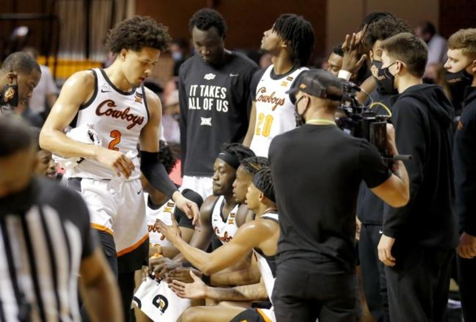 Photo -  Oklahoma State's Cade Cunningham, left, talks with teammates during a timeout Tuesday in the 75-70 uspet of No. 6-ranked Kansas. [Sarah Phipps/The Oklahoman]