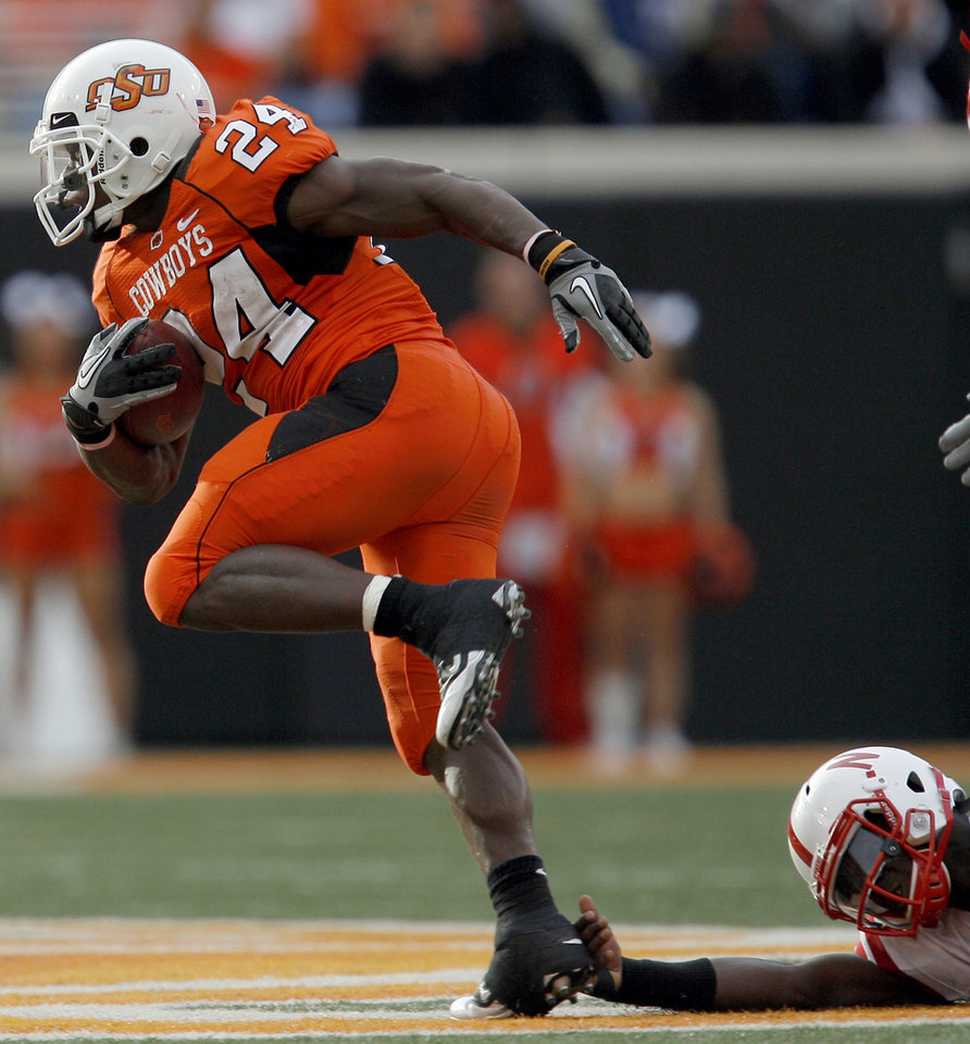 Photo - OSU's Kendall Hunter slips past a Nebraska defender during the college football game between the Oklahoma State Cowboys (OSU) and the Nebraska Huskers (NU) at Boone Pickens Stadium in Stillwater, Okla., Saturday, Oct. 23, 2010. Photo by Sarah Phipps, The Oklahoman