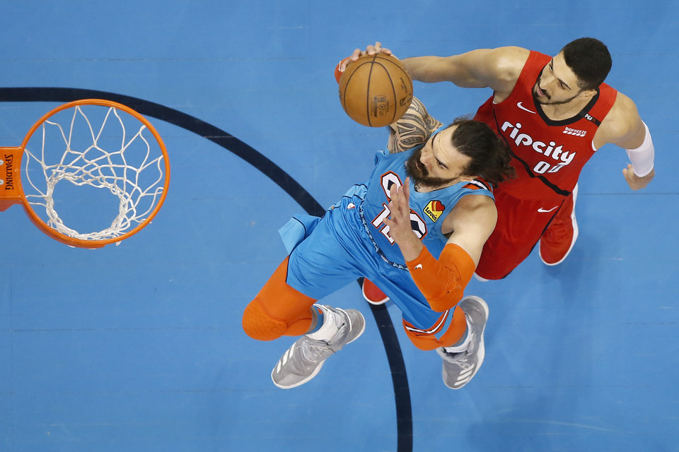 Photo - Oklahoma City's Steven Adams (12) goes to the basket past Portland's Enes Kanter (00) during Game 3 in the first round of the NBA playoffs between the Portland Trail Blazers and the Oklahoma City Thunder at Chesapeake Energy Arena in Oklahoma City, Friday, April 19, 2019. Photo by Bryan Terry, The Oklahoman