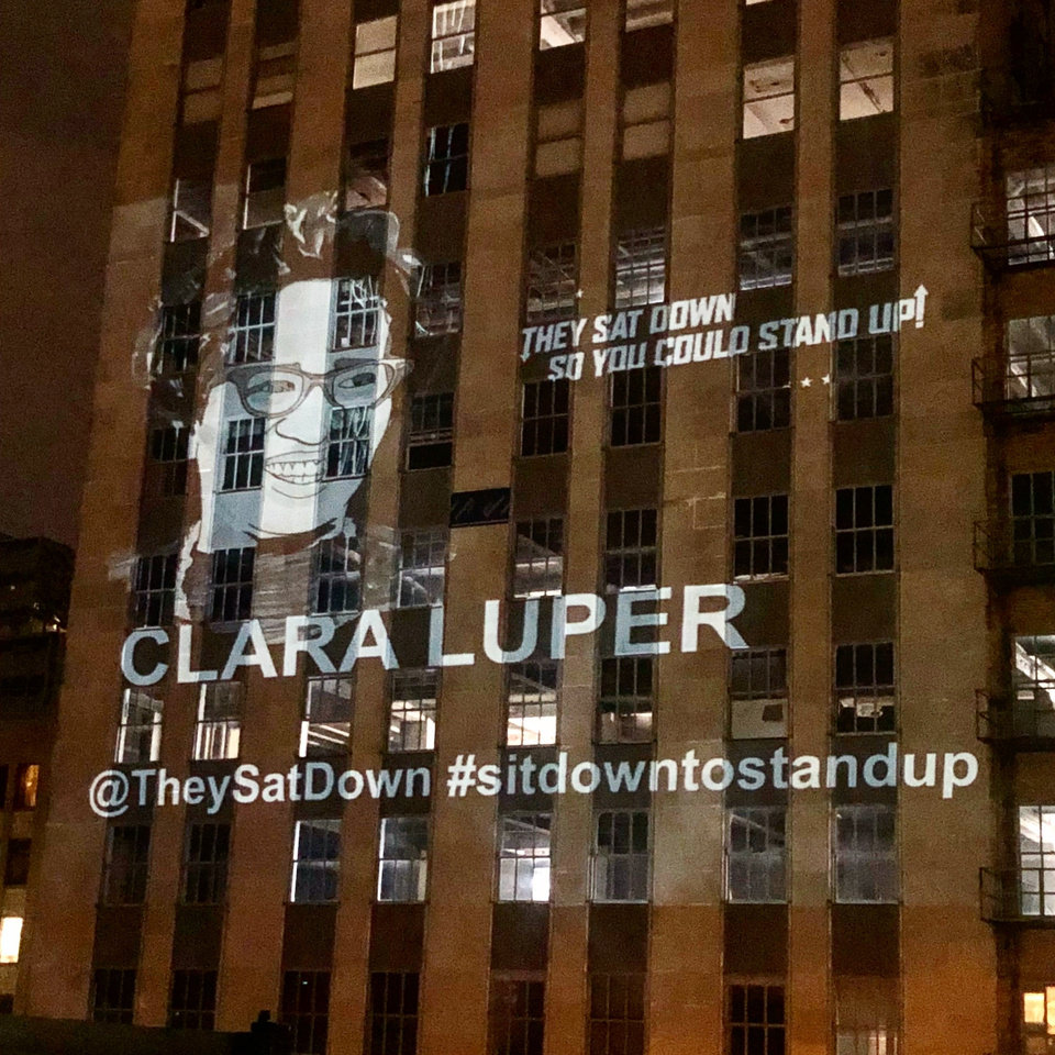 Photo -  A portrait of civil rights icon Clara Luper, created by artist Jack Fowler, was projected Saturday night on the south side of First National tower overlooking the site of Aug. 19, 1958, sit-ins at Katz Drug Store. [Photo provided by Stephen Tyler]