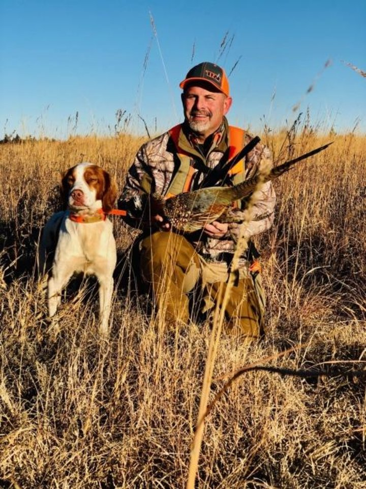 Photo -  Steve Easom of Slaughterville and his dog, Jude, pose for a photo after a pheasant hunt last season in north-central Oklahoma. The state's two month pheasant season opened Dec. 1. [PHOTO PROVIDED]