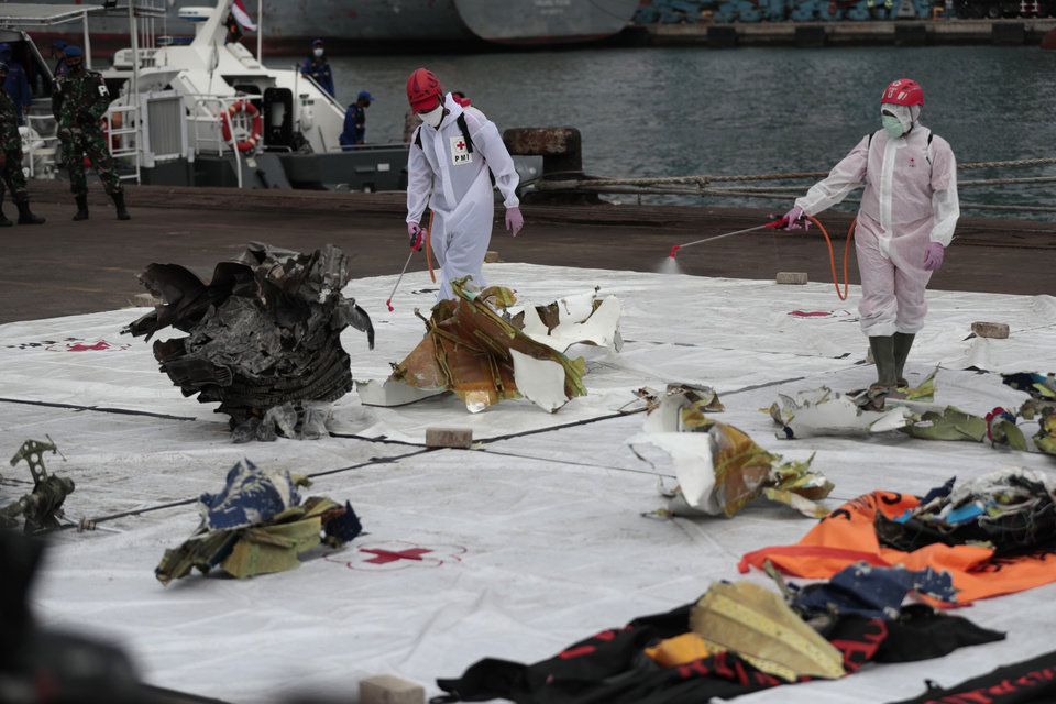 Photo -  Workers spray disinfectant at parts of aircraft recovered from Java Sea where a Sriwijaya Air passenger jet crashed, at Tanjung Priok Port in Jakarta, Indonesia, Monday, Jan. 11, 2021. The search for the black boxes of a crashed Sriwijaya Air jet intensified Monday to boost the investigation into what caused the plane carrying dozens of people to nosedive at high velocity into the Java Sea. (AP Photo/Dita Alangkara)