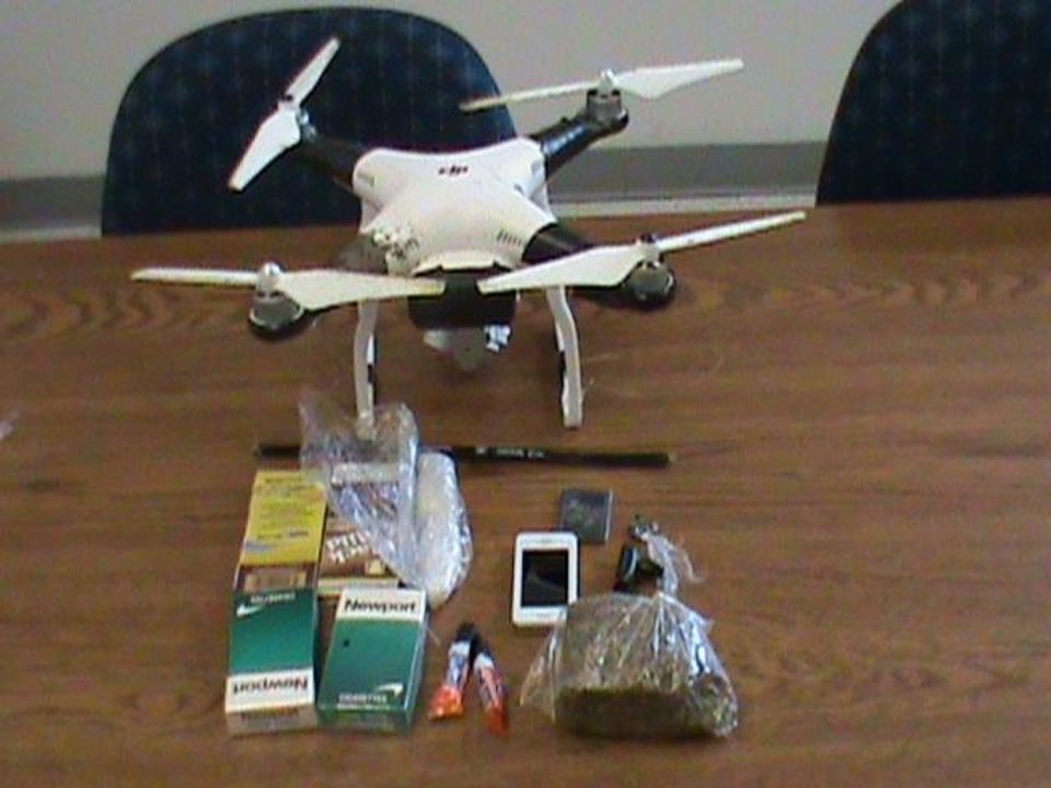 Photo -  A drone that crashed after catching the wire fence around the Oklahoma State Penitentiary in McAlester on Oct. 26, 2015. The drone carried a package that included super glue, a cellphone and battery, cigars and cigarettes, methamphetamine, heroin, marijuana, and hacksaw blades. Photo provided by the Oklahoma Department of Corrections.