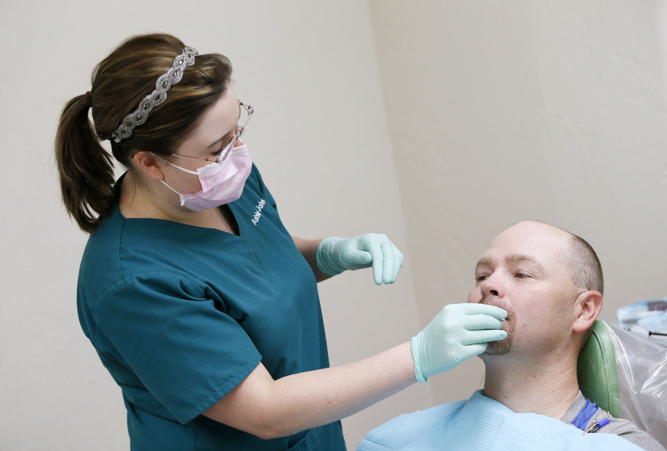Photo -  Ashley Johnson, a fourth-year dental student at the University of Oklahoma, works with patient John Nelson at the Open Wide Dental Clinic at Portland Avenue Baptist Church, 1301 N Portland Ave. in Oklahoma City. [Photo by Nate Billings, The Oklahoman]