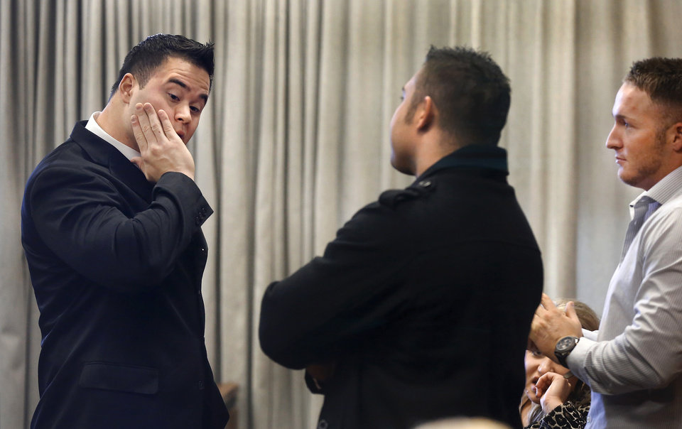 Photo - Daniel Holtzclaw rubs his face as he talks with two men seated in the spectator area during a brief break in his preliminary hearing. Three women testified in an Oklahoma County courtroom   that an Oklahoma City police officer sexually assaulted them while the officer was on duty. The women testified Monday , Nov. 17, 2014, during a preliminary hearing for 27-year-old Daniel Holtzclaw, who is accused of 32 counts of rape, sexual battery and other charges involving 13 women. Holtzclaw has pleaded not guilty.   Photo by Jim Beckel, The Oklahoman