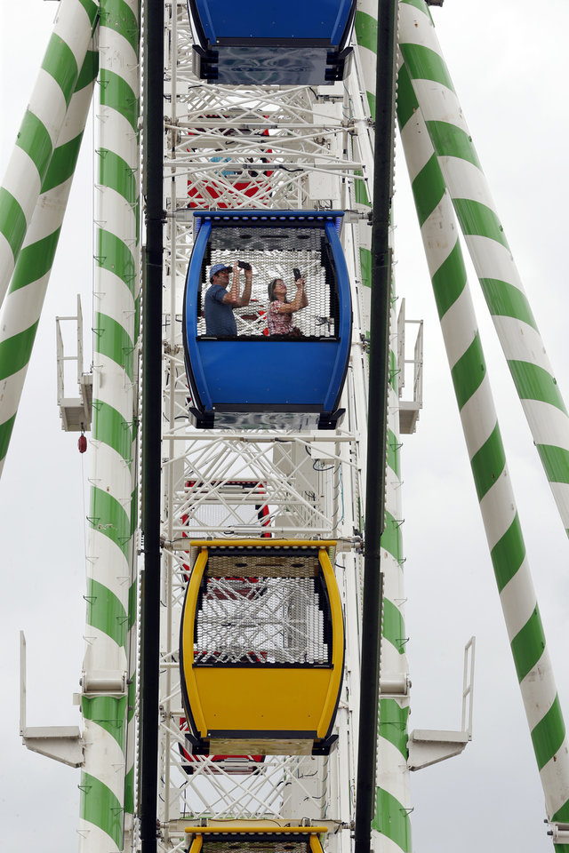 Photo -  Fairgoers ride the giant Ferris Wheel at the Oklahoma State Fair on Thursday.