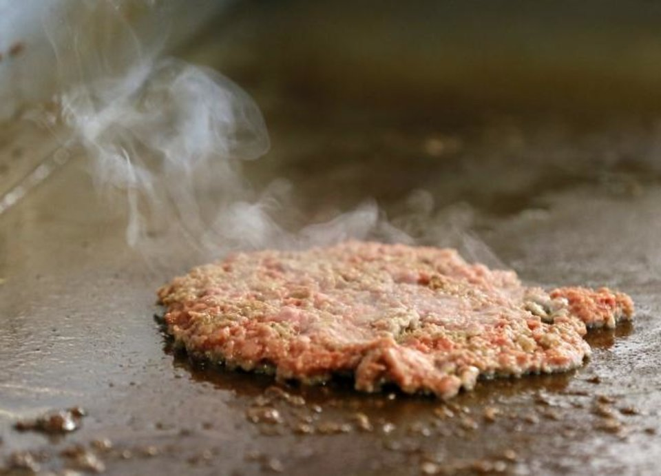 Photo -  An Impossible Burger patty is cooked for the plant-based Impossible Melt at Wayback Burgers in Edmond. [Nate Billings/The Oklahoman]
