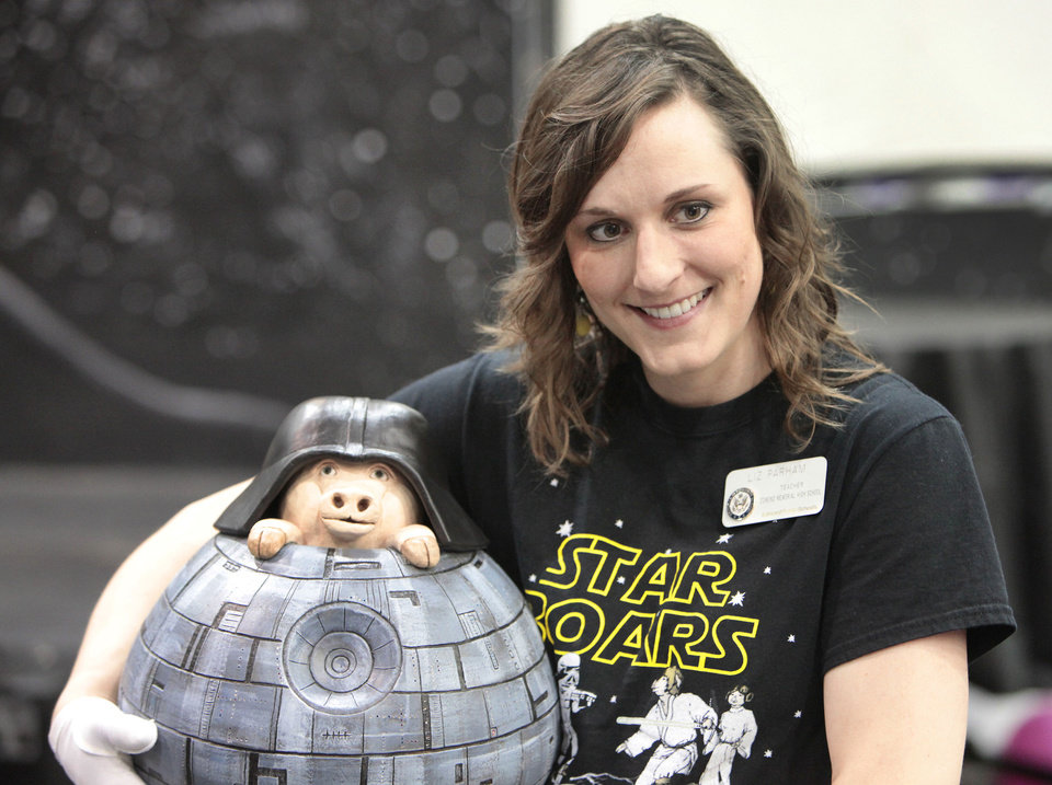 Photo - Art Teacher Liz Parham holds the Death Star Piggy Bank she made to raise money for Swine Week. The bank was auctioned for $8,000. Photo By David McDaniel/The Oklahoman  David McDaniel - The Oklahoman