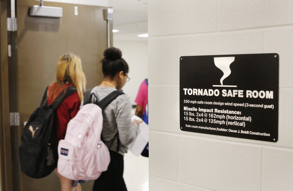 Photo -  High school students are shown leaving a wing added to Moore High School that doubles as a safe room. [Photo by Jim Beckel, The Oklahoman]